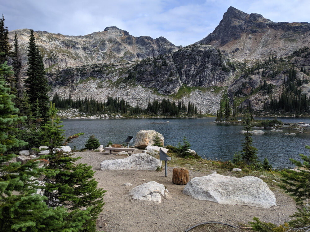 Looking towards designated cooking area in Gwillim Lakes campground, with rocks, benches and cook stove tables