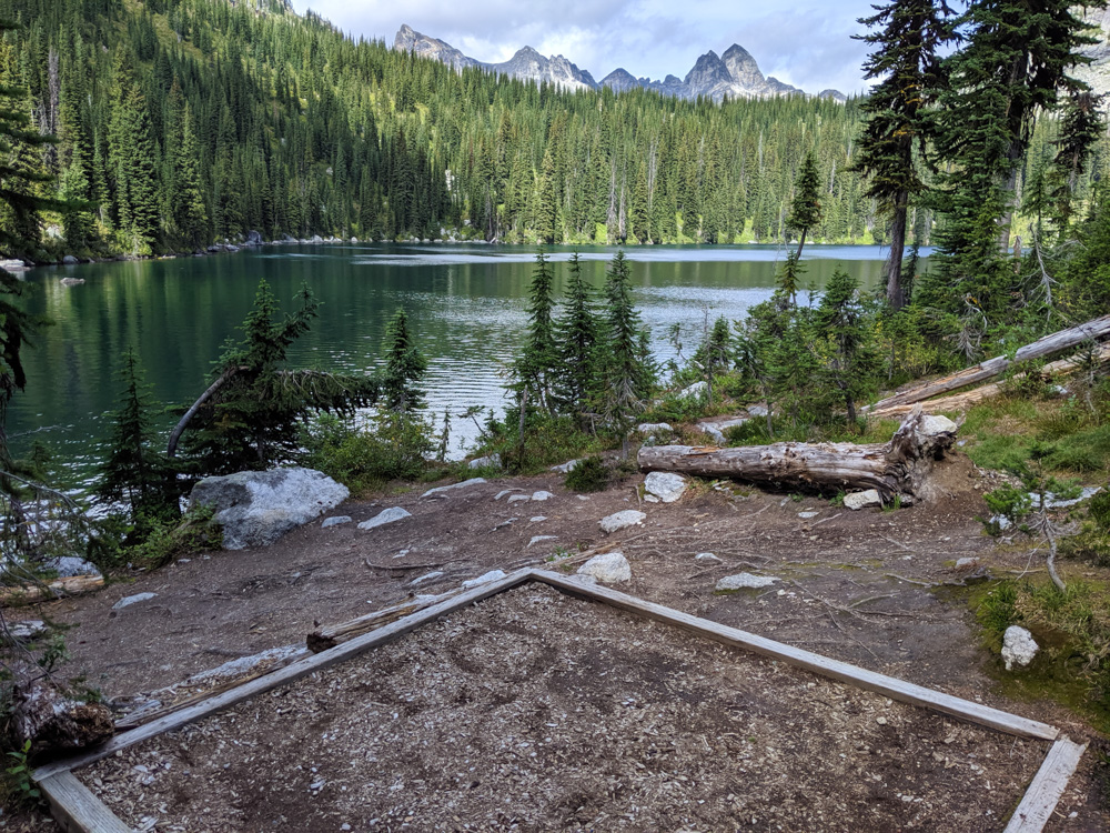 A tent pad next to Drinnon Lake with views of the turquoise water and dramatic mountain summits just peeking over the forest line