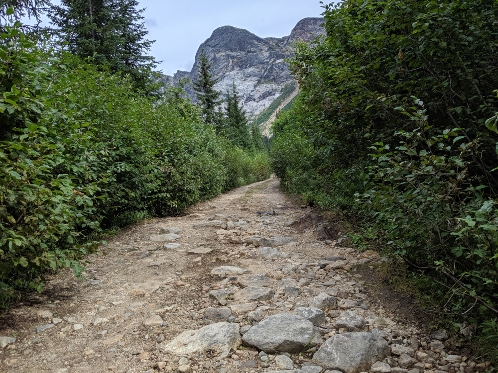Looking up a narrow and rocky section of road with mountain backdrop