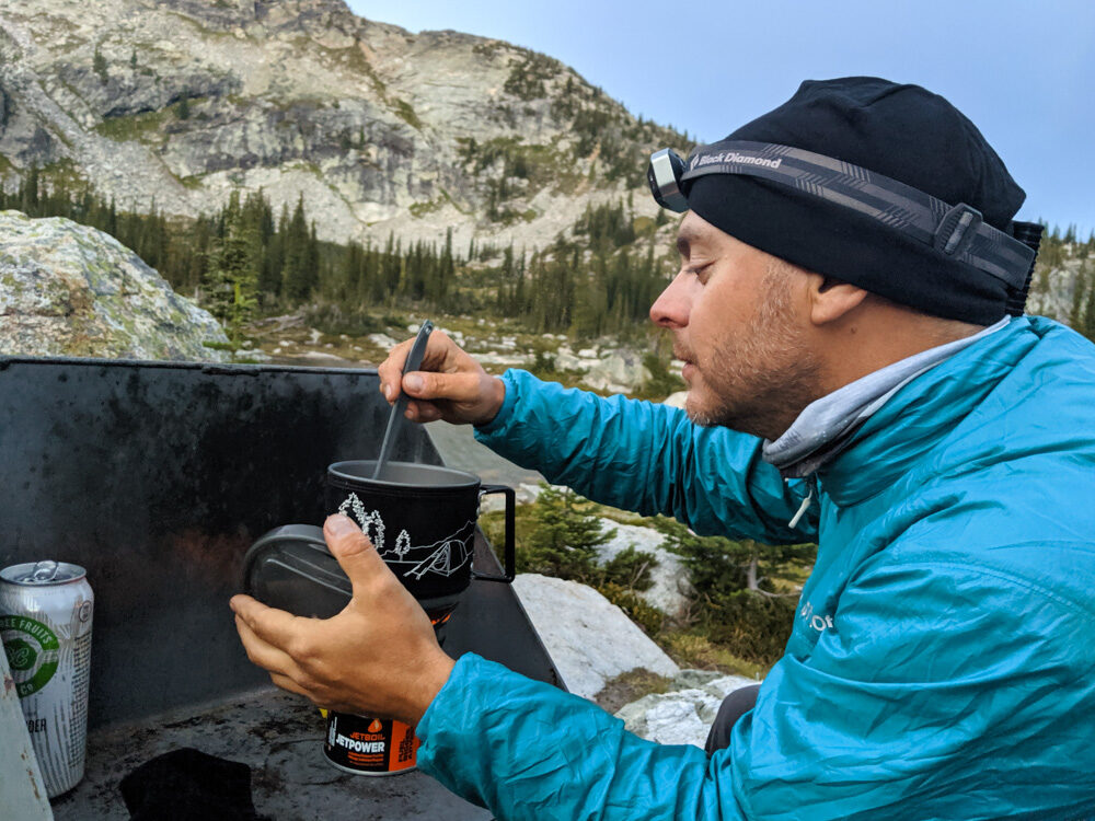 Side view of JR cooking a meal in the Jetboil stove in alpine location