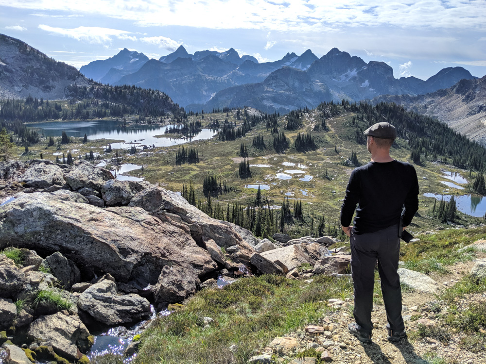 JR standing in front of beautiful views of lakes and mountains in the Gwillim Lakes area of Valhalla Provincial Park