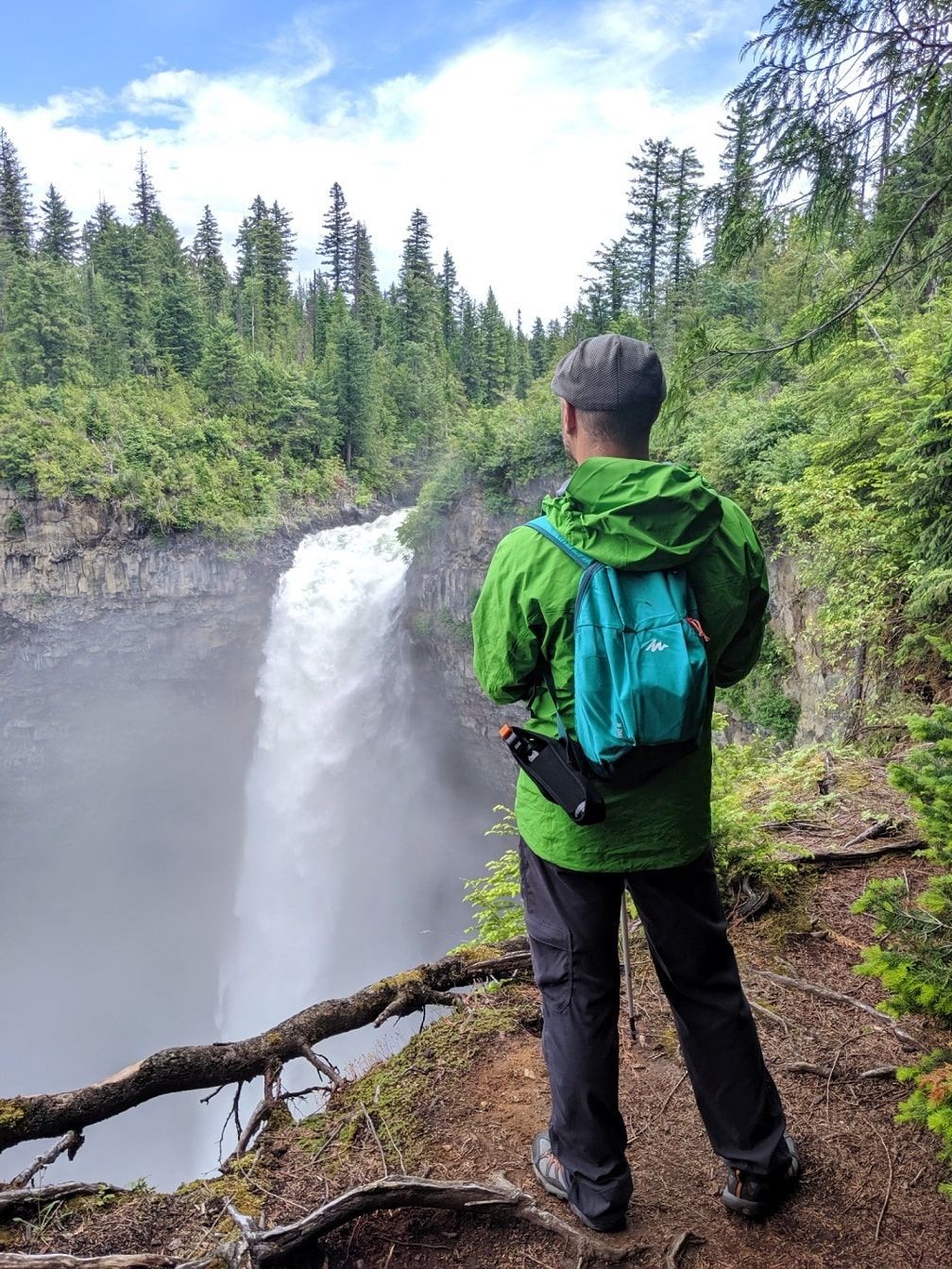 JR standing in front of Helmcken Falls in a green jacket and green backpack