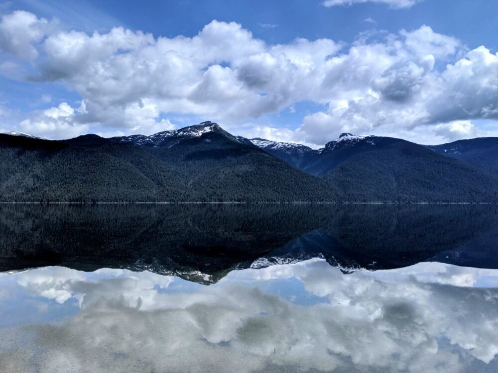 Mirror lake reflections of snow capped mountains on Murtle Lake, one of the best BC canoe trips