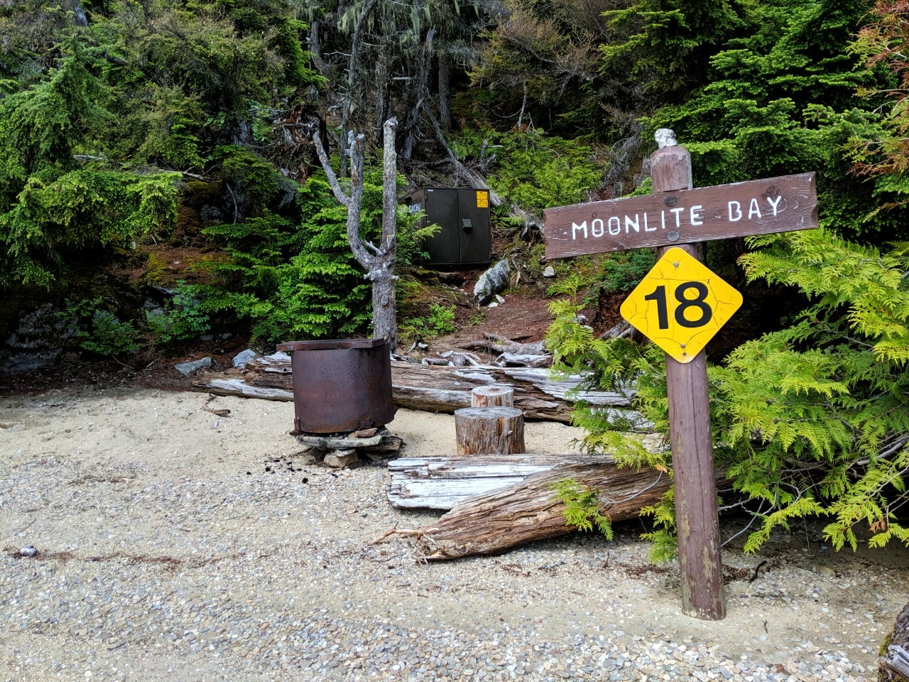 Beach view of Moonlite Bay campsite with yellow sign, fie pit and food cache in background