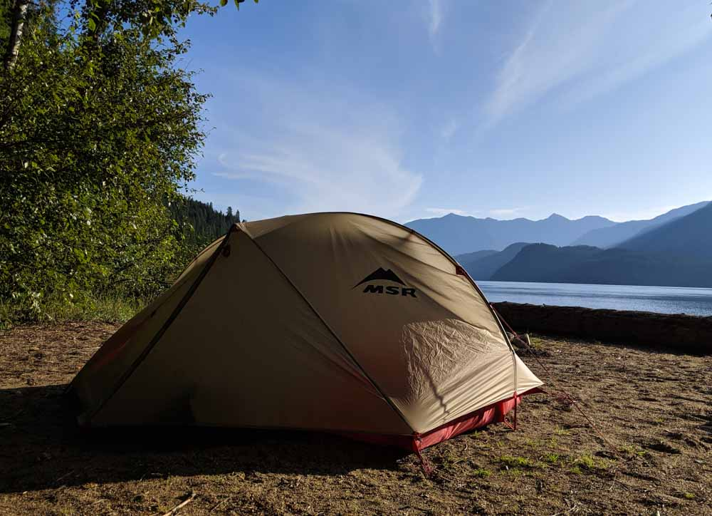 Msr freelite tent set up sandy beach with mountains in the background