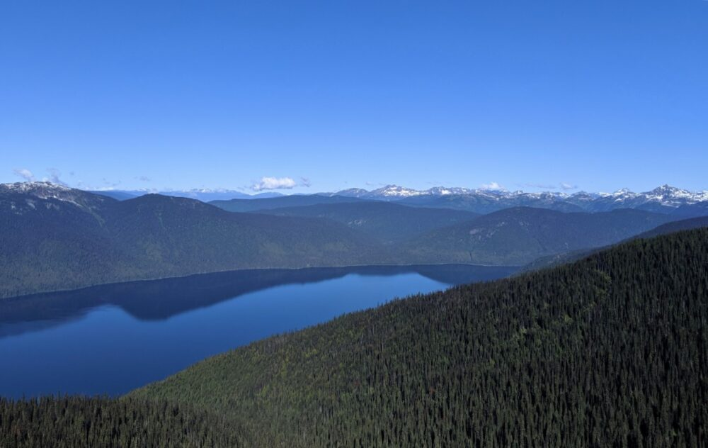 Looking down from alpine ridge to Murlte Lake, a huge deep blue lake backdropped by snow capped mountains. Murtle Lake offers one of the best bc canoe trips