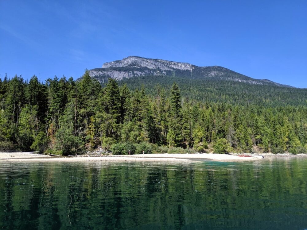 Water view looking over to one of Slocan Lake's golden sand beaches, with a backdrop of forest and mountains