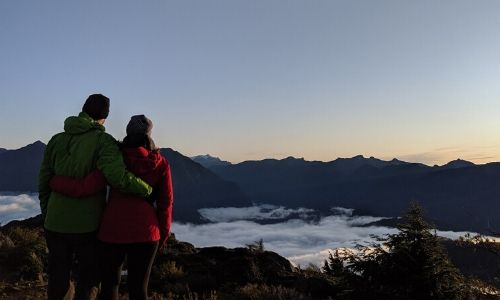 Gemma and JR standing with backs to camera looking towards sunrise on mountain, wearing colourful jackets