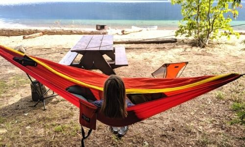Orange red and yellow hammock strung between two trees with Gemma sat in the middle, looking out to the lake