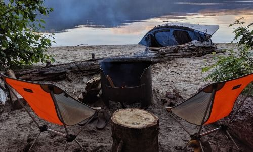 Two lightweight orange camp chairs set up in front of campfire with lake and canoe behind