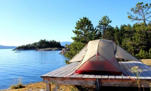 Tent set up on wooden tent platform next to ocean