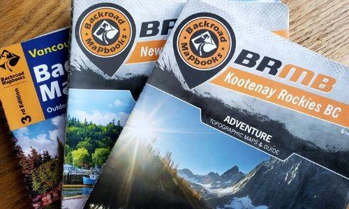 three backroad mapbooks on table