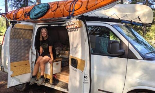 Gemma sat inside white van with kayaks on roof