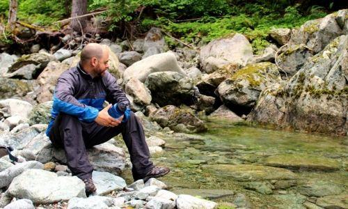 JR sat on rock next to creek holding water bottle