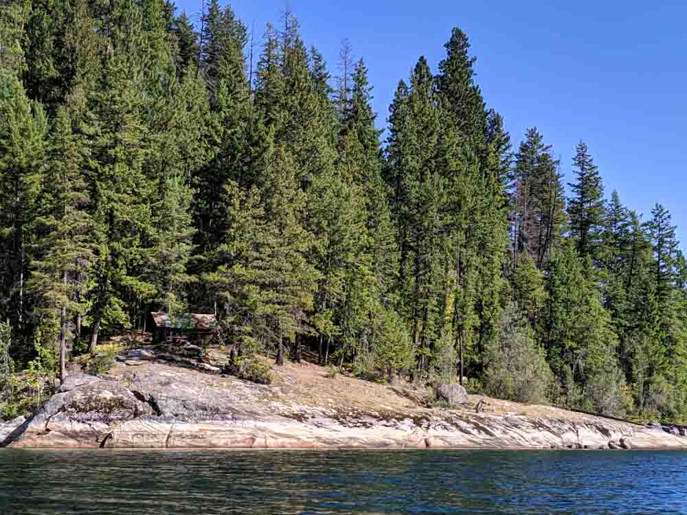 Rocky headland above Slocan Lake with cabin set into forest