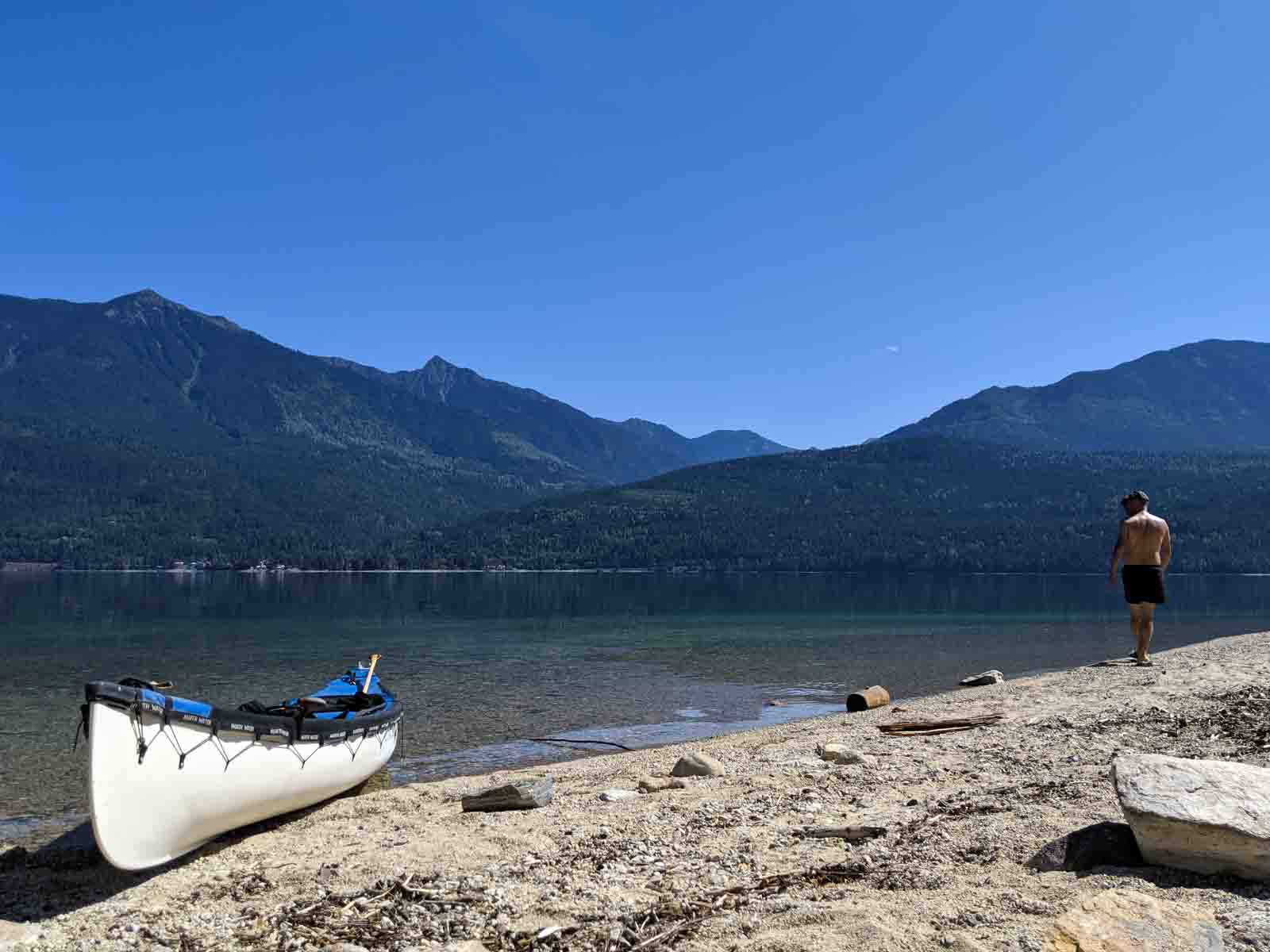 JR standing on beach with canoe resting on shore next to calm lake with mountains behind