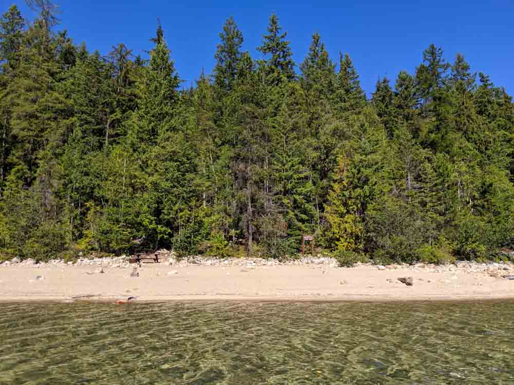 Water view of golden sand beach lined by forest - Indian Creek campground on Slocan Lake, Valhalla Provincial Park