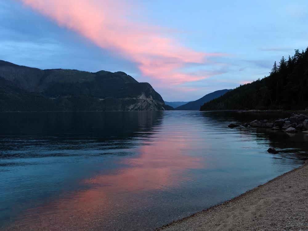 Looking from the beach towards a pinkish sunset on the southern end of Slocan Lake
