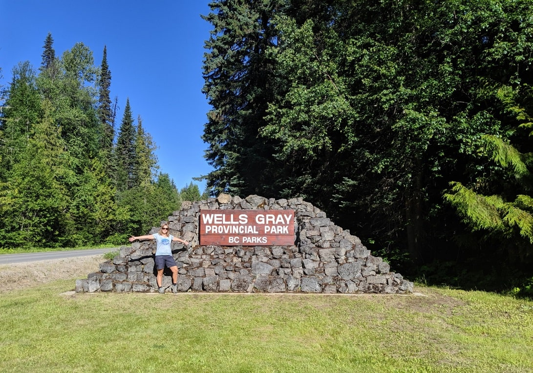 Stone and wood Wells Gray Provincial Park sign with Gemma standing in front