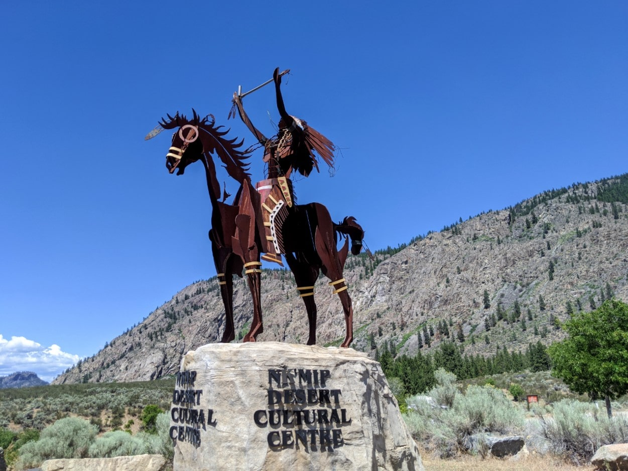 Metal sculpture of horse and rider on rock plinth at the Nk'Mip Desert Cultural centre
