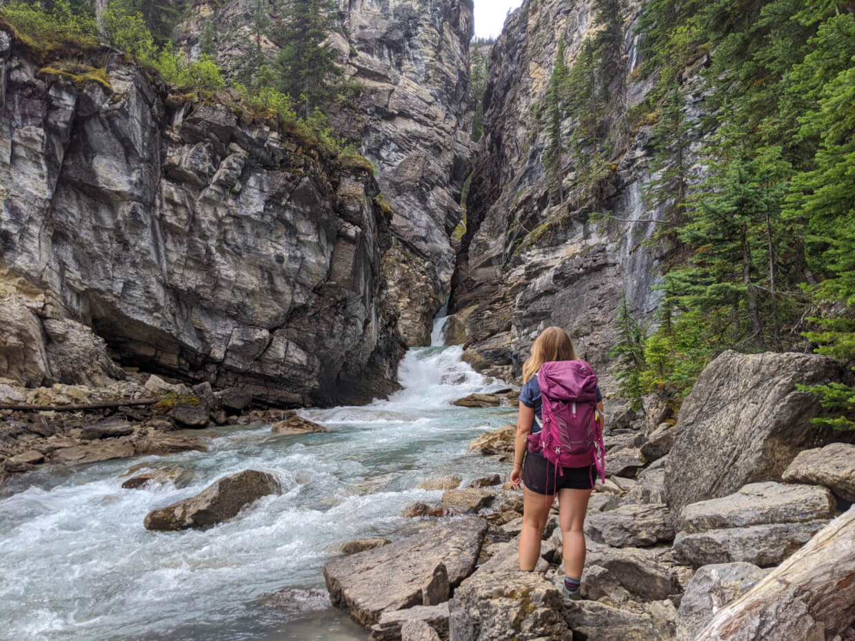 Gemma stands wearing pink backpack with back to camera, standing on rocky surface looking at water rushing through rocky canyon