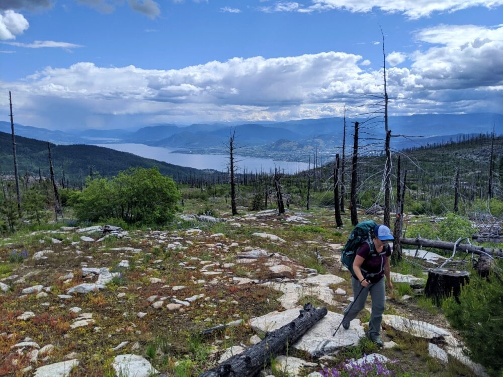 Gemma hiking on Divide Lake trail with panoramic views of Okanagan Lake and surrounding mountains behind