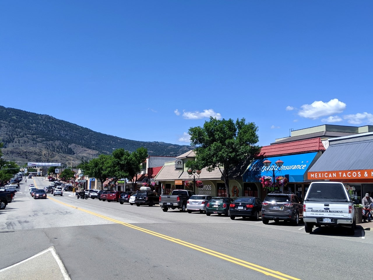Downtown Osoyoos with parked cars on right hand side in front of stores