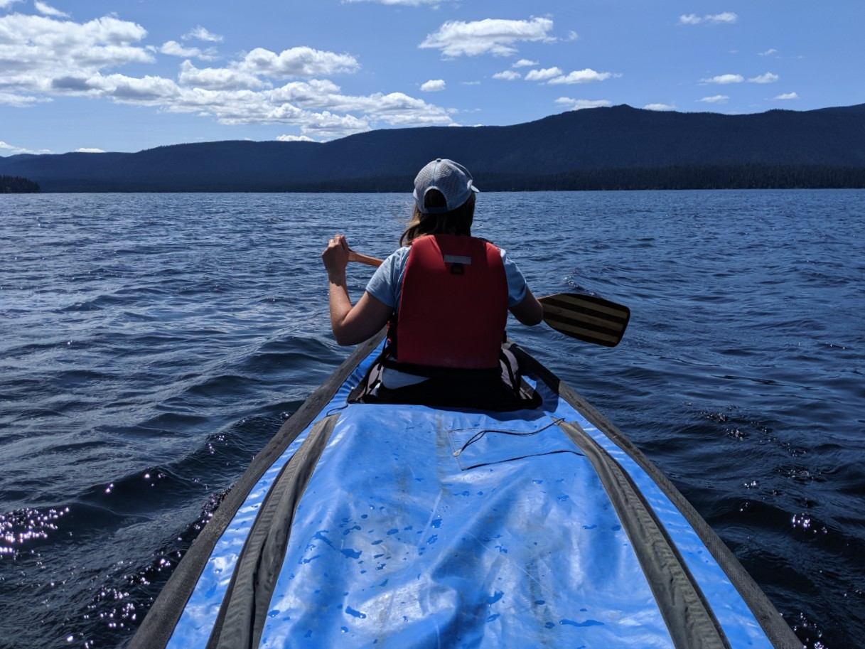 Back view of Gemma paddling canoe  on Murtle Lake in Wells Gray Provincial Park