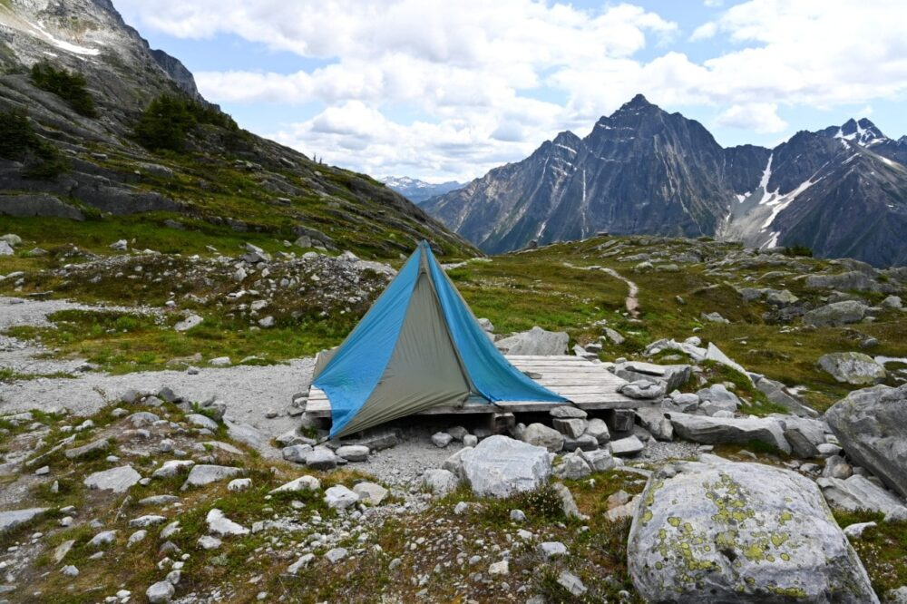 Blue and grey tent on wooden tent pad in alpine area with meadows and mountain backdrop in Glacier National Park, Canada
