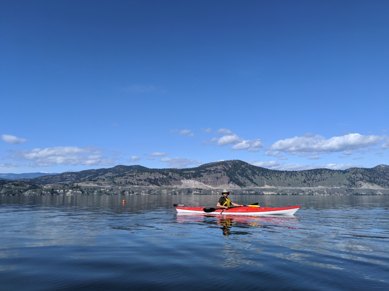 JR in red kayak on calm lake with Summerland in background