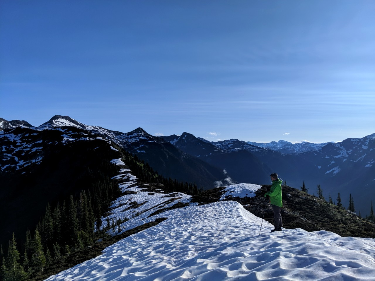 JR standing on snowy mountain ridge looking towards surrounding mountains