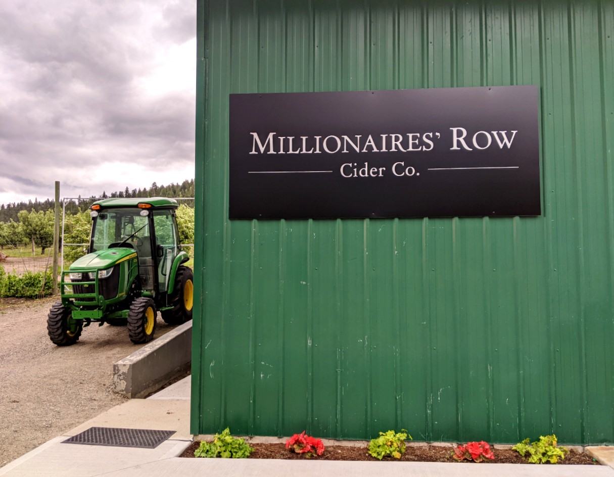 Edge of green industrial building with Millionaires Row cider Co sign, tractor parked next to building