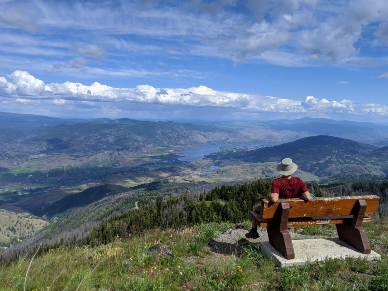 JR at on bench looking out to elevated view of Osoyoos set into rolling hills and vineyards