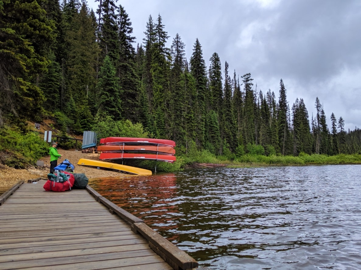 Looking back on Murtle Lake wooden dock with backpacks and canoe in front of beach with rental canoe rack
