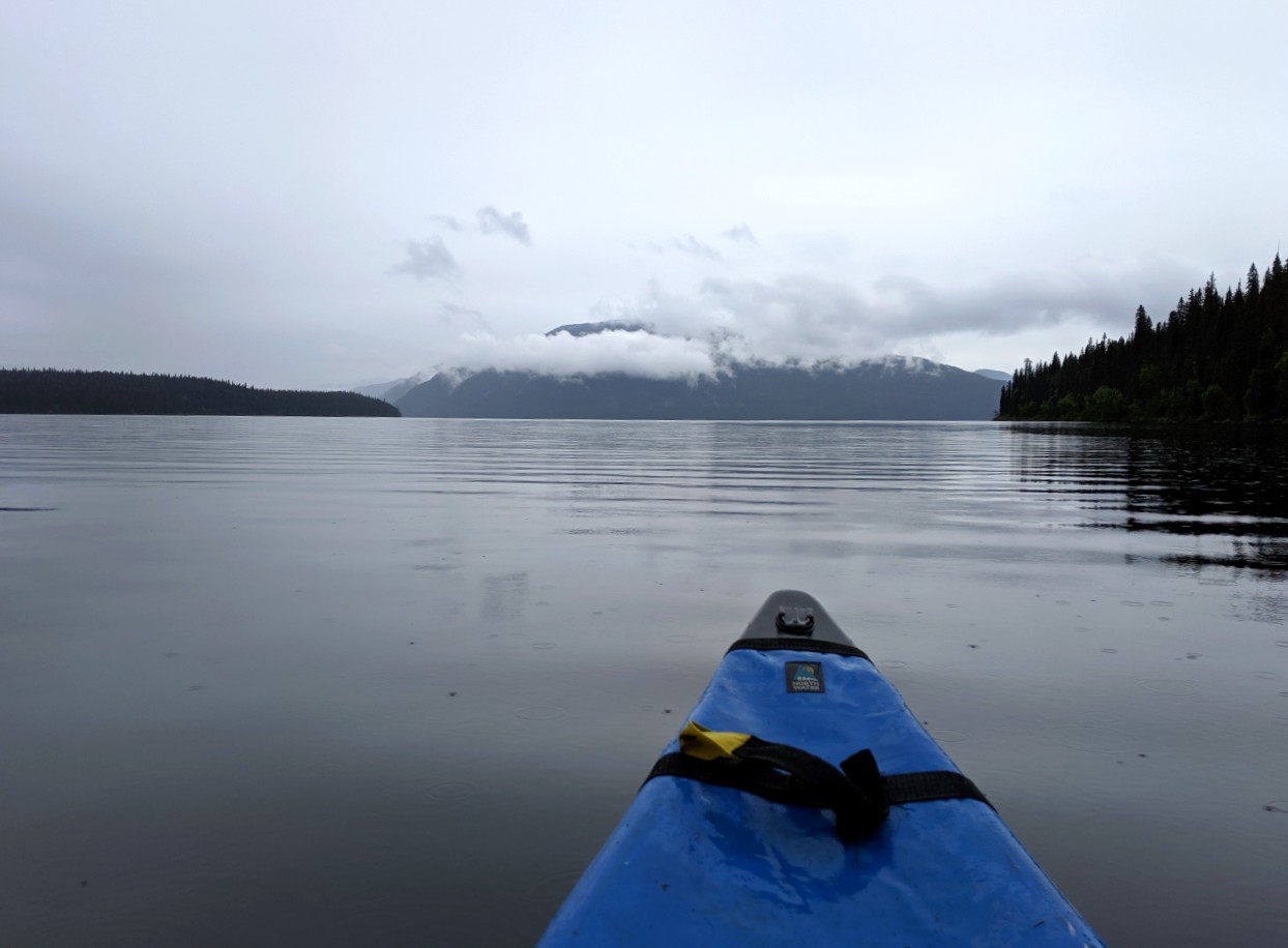 Canoe view of calm lake with overcast skies and mist