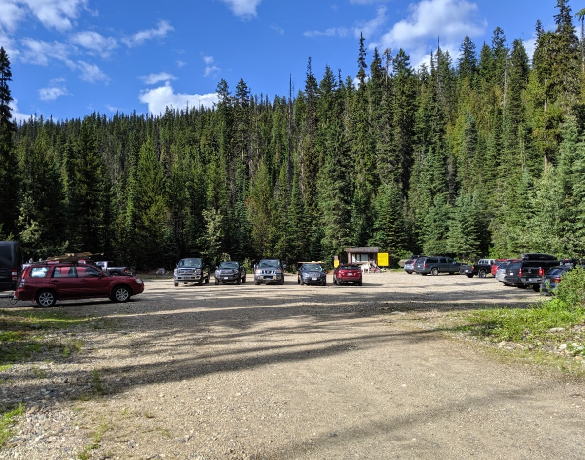 Gravel parking at Murtle Lake with approximately 20 or so vehicles parked, surrounded by forest