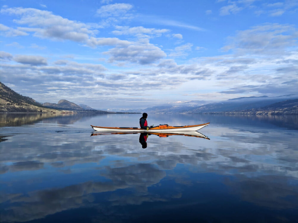 Orange and white kayak on water in middle of Okanagan Lake, paddler is wearing red PFD and is looking into the distance. The sky is reflected on the lake's surface and the backdrop is rolling mountains