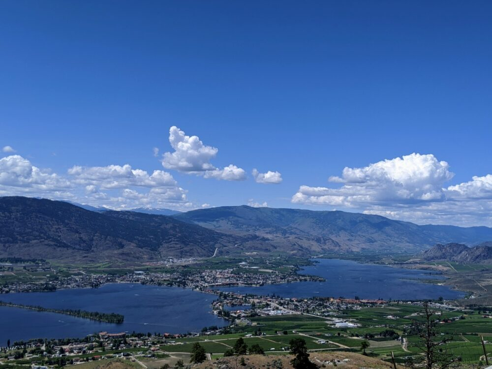 Elevated view looking down on the town of Osoyoos next to Osoyoos Lake with hills and mountains in the background