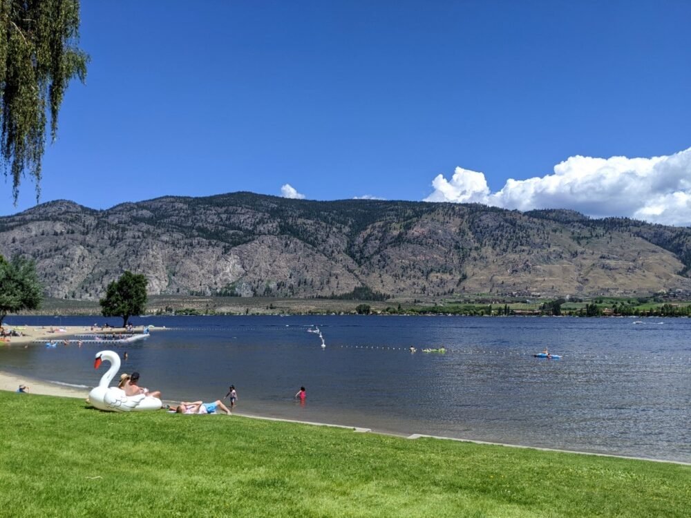 Osoyoos Lake shore with people swimming and grass border