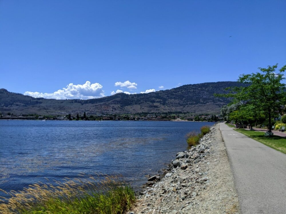 Paved cycle path next to Osoyoos Lake with rolling hills behind