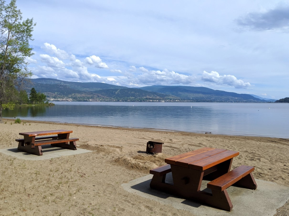 Two picnic tables on sandy beach with firepit next to calm lake and Naramata and Penticton beyond