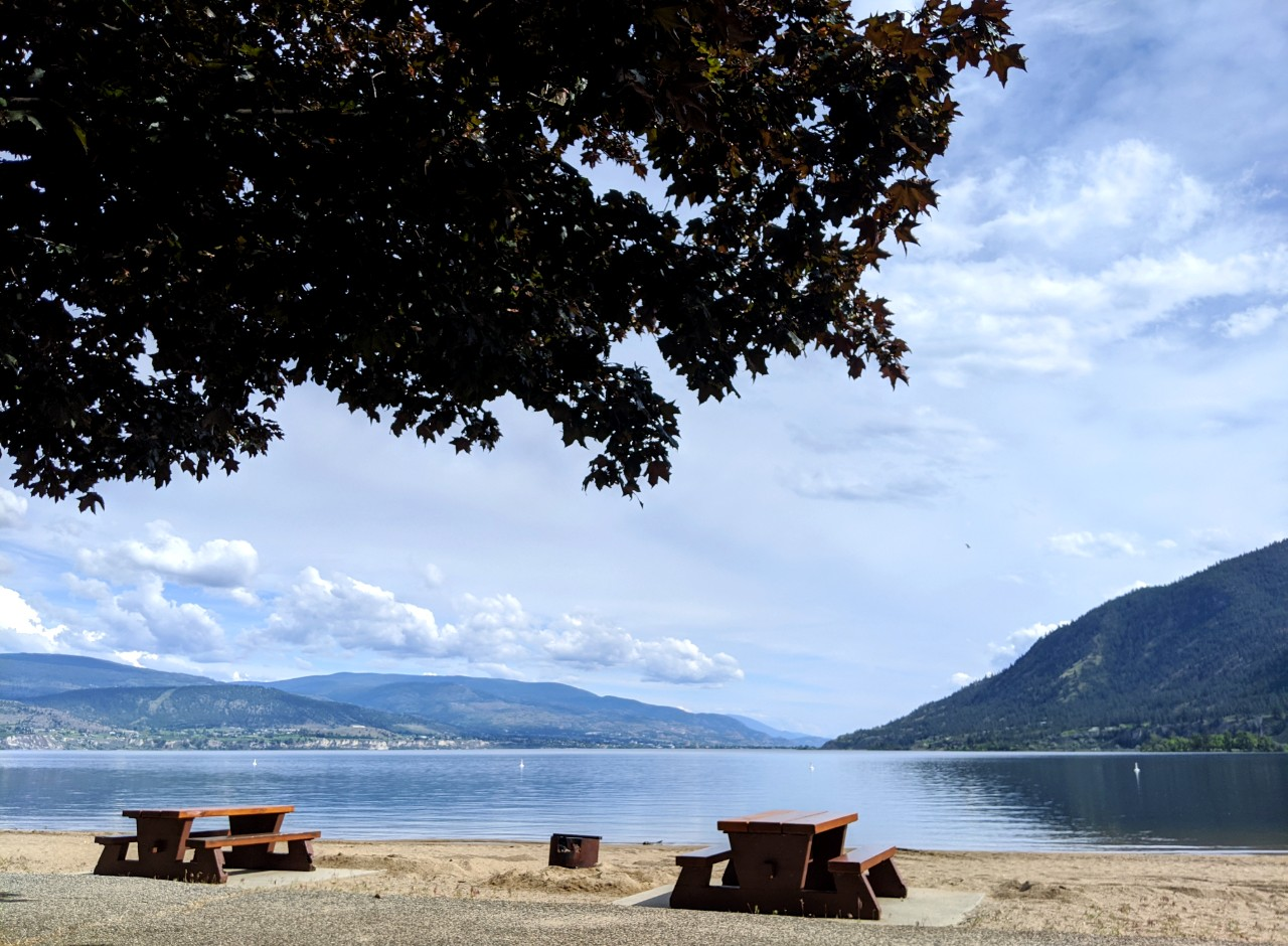 Sandy beach with two picnic tables and firepit next to calm lake in Summerland