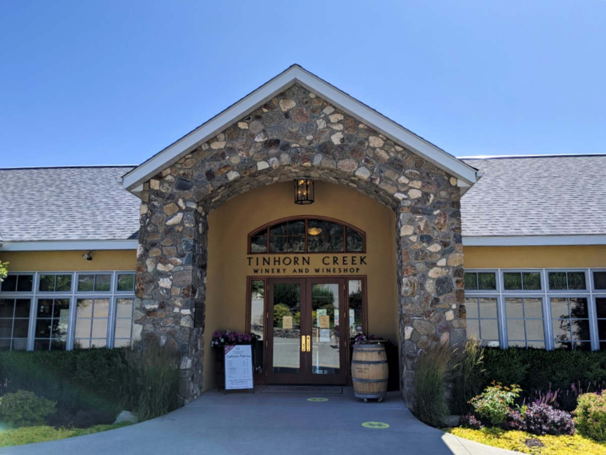 Tinhorn Creek Winery entrance with stone arch and wine barrel