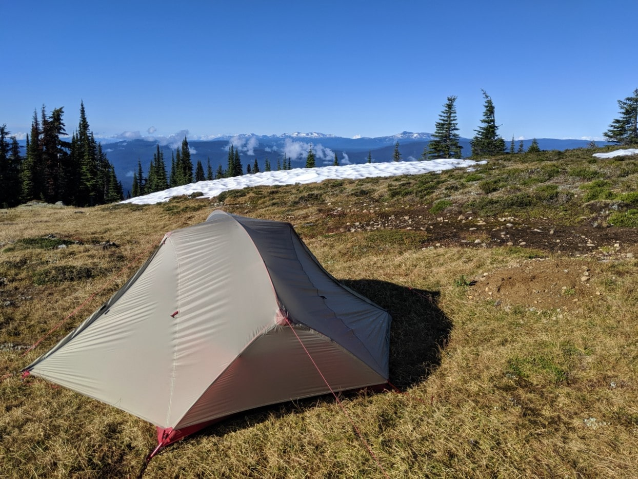 Set up tent in alpine area above Murtle Lake with snow capped mountains in backgound