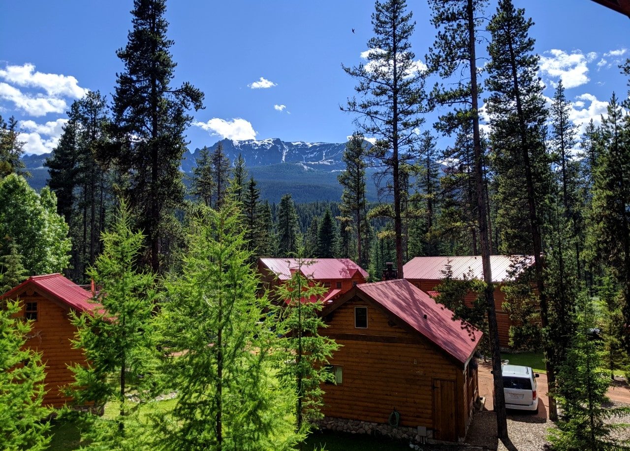 Balcony view of red roofed cabin buildings with snow capped mountains in background at Baker Creek Mountain Resort