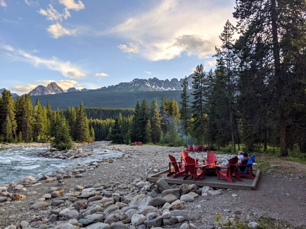 Firepits with red Adirondack chairs next to river, backdropped by mountains