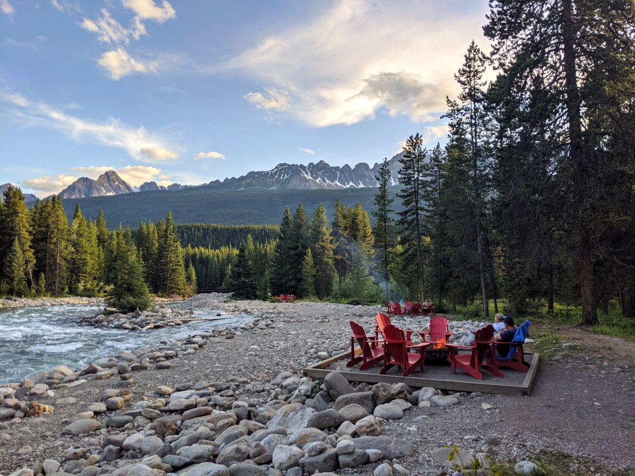 Firepits and red Adirondack chairs set next to rushing Baker Creek, backdropped by mountains