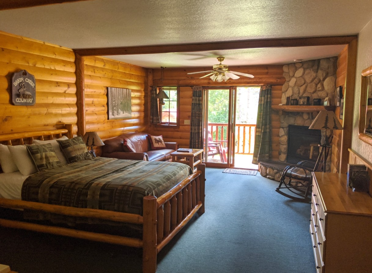 Lodge room at Baker Creek Mountain Resort with wooden furnishings, stone gas fireplace and balcony