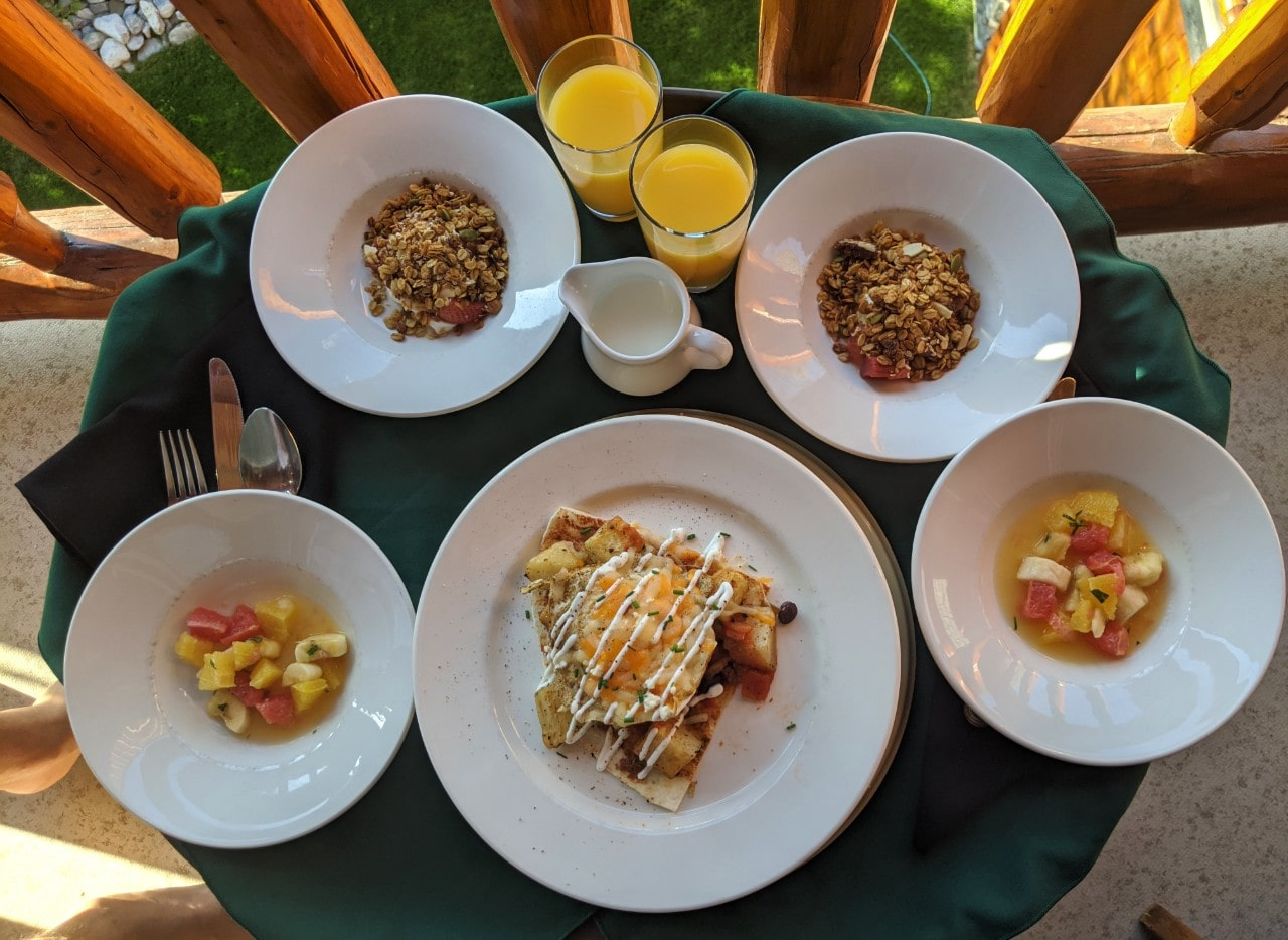 Overview look of breakfast dishes with orange juice, granola, fruit bowl and cooked egg/potato dish at the Bear and Bison Inn