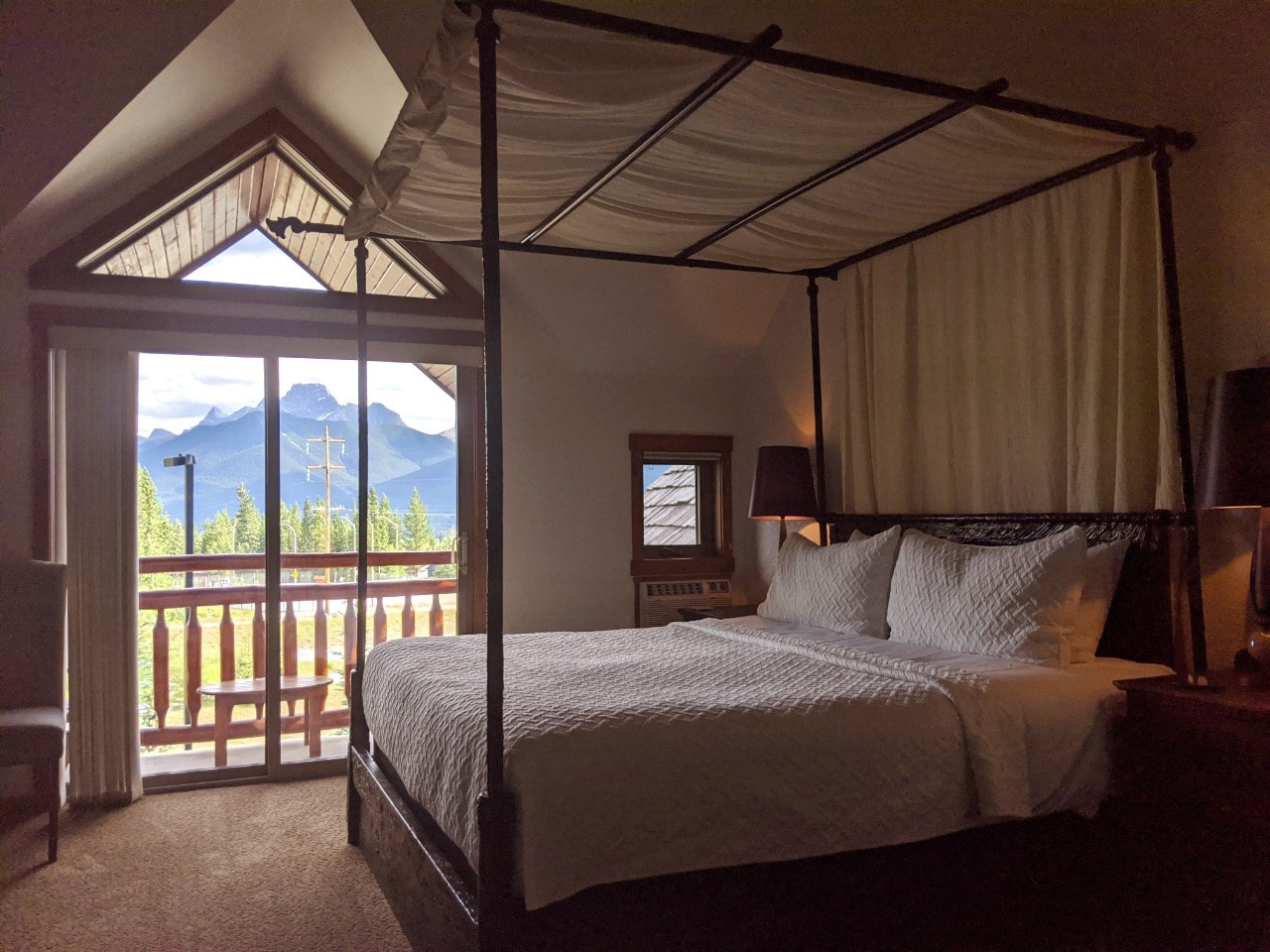 Bear and Bison Inn room featuring four poster bed and balcony in background with mountain views